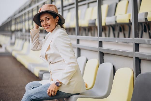 帽子を保持している白いジャケットの若い女性