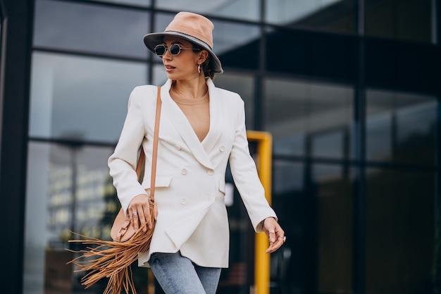 屋外を歩く白いジャケットの若い女性