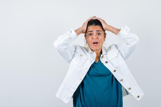 Молодая женщина в белой джинсовой куртке с головой с руками и тревожно глядя, вид спереди.
