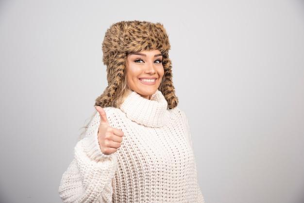 엄지 손가락을 포기하는 흰색 니트 스웨터에 젊은 여자.