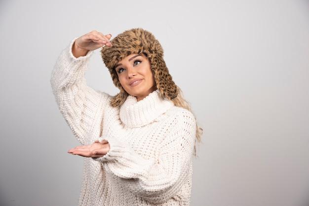 열린 공간을 잡고 흰색 니트 스웨터에 젊은 여자.