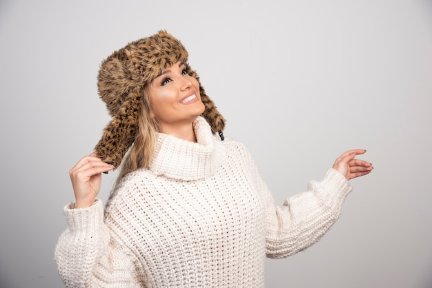 흰색 니트 스웨터 찾고 행복에 젊은 여자.