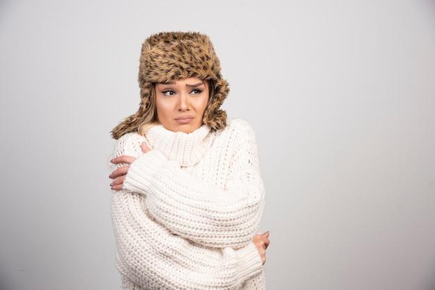 흰색 니트 스웨터 찾고 무서 워 젊은 여자.