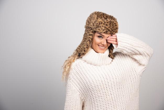회색 배경에 포즈 흰색 니트 스웨터에 젊은 여자.