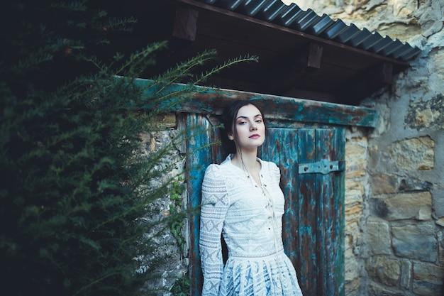 田舎の小屋の近くの白いレースの長袖ブラウスの若い女性