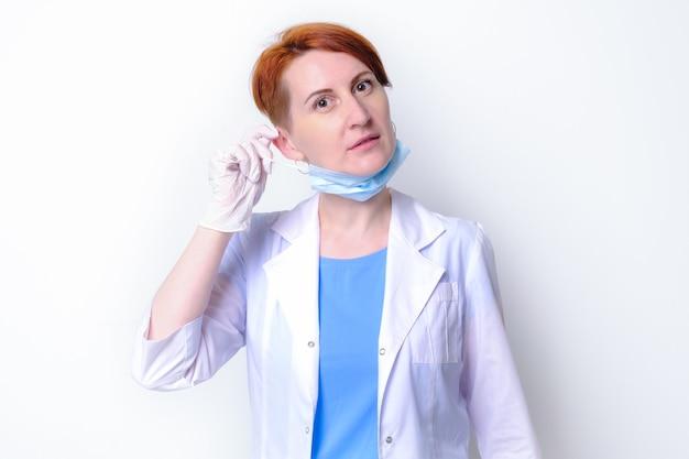 白い医療用ガウンを着た若い女性が医療用マスクを脱いでいます。女医師の肖像