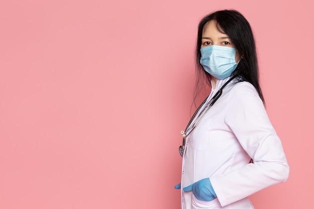 Молодая женщина в белом медицинском костюме синие перчатки голубая защитная маска на розовом