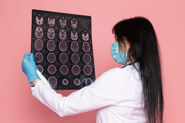 흰색 의료 소송에서 젊은 여자 파란색 장갑 파란색 보호 마스크 핑크 청진