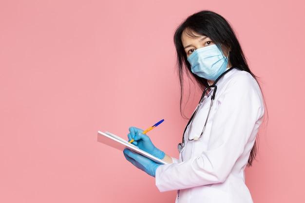 Молодая женщина в белом медицинском костюме синие перчатки синие защитные маски с стетоскопом заметок на розовом