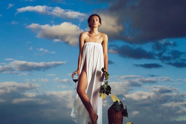 青い空の上の自然のガラス籐のボトルのつるとブドウの赤ワインと白いセクシーなドレスの若い女性