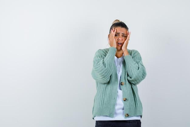 흰 셔츠와 민트 그린 카디건을 입은 젊은 여성이 뺨에 손을 대고 스트레스를 받고 있다