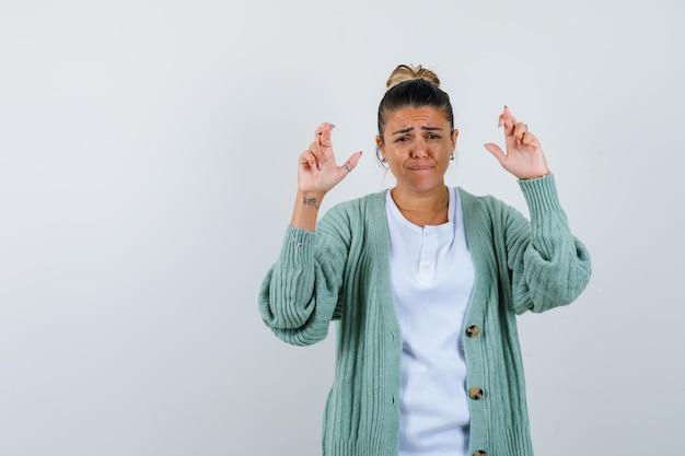 白いシャツとミントグリーンのカーディガンを着た若い女性が指を交差させて急いでいるように見える