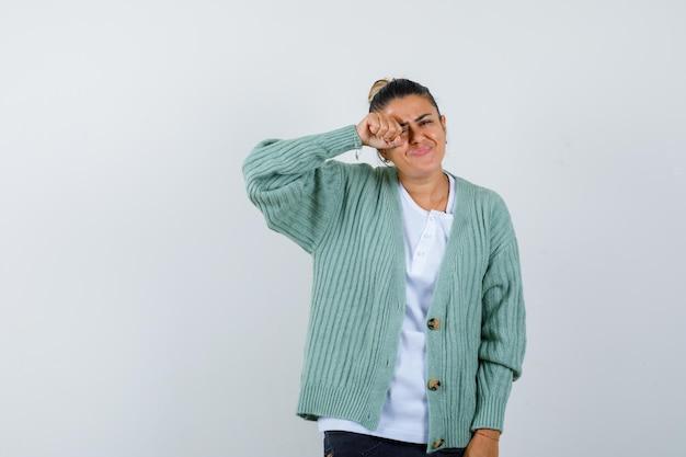 Молодая женщина в белой рубашке и мятно-зеленом кардигане протирает глаза и выглядит усталой