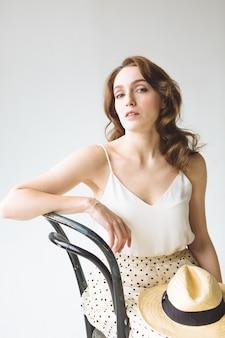 白いシャツと白い背景の上の帽子とスカートの若い女性