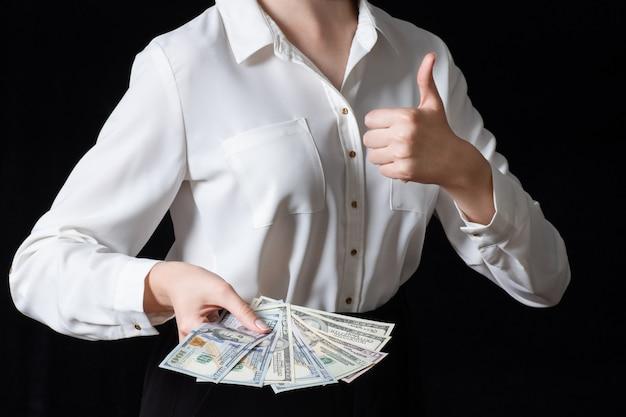Молодая женщина в белой рубашке держит 100-долларовые банкноты, делая знак ок