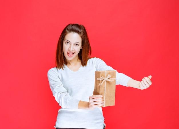 段ボールのギフトボックスを保持し、肯定的な手のサインを示す白いシャツの若い女性