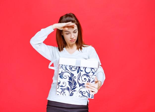 인쇄된 선물 상자를 들고 흰색 셔츠를 입은 젊은 여성이 불만족스럽고 화난 것처럼 보입니다.