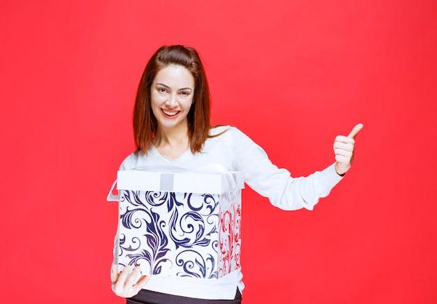 印刷されたギフトボックスを保持し、肯定的な手のサインを示す白いシャツの若い女性