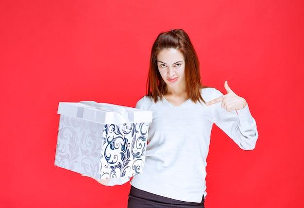 인쇄된 선물 상자를 들고 흰 셔츠에 젊은 여자