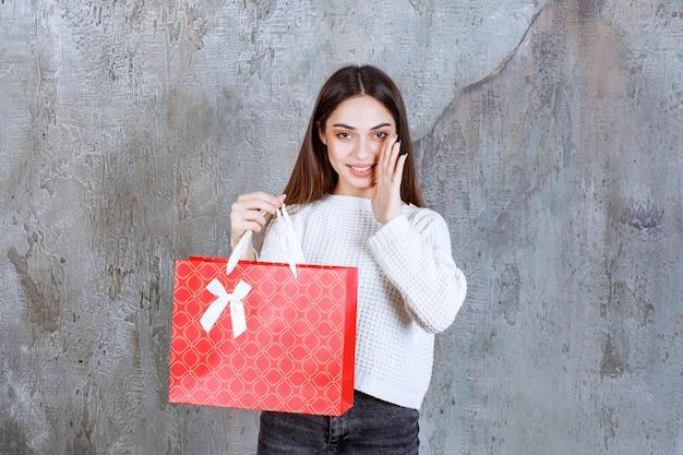 Молодая женщина в белой рубашке держит красную сумку для покупок и сплетничает