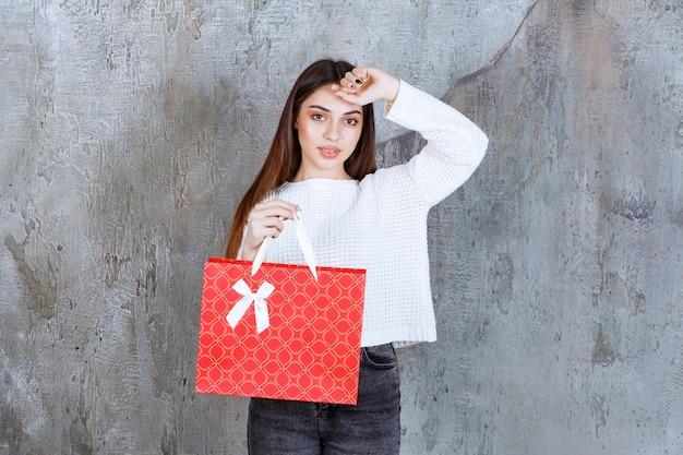 Молодая женщина в белой рубашке держит красную сумку для покупок и выглядит смущенной и задумчивой