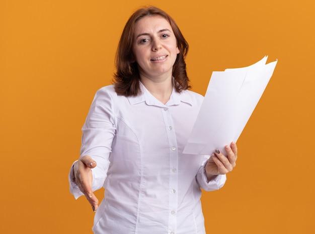 오렌지 벽 위에 서 웃는 인사를 앞에보고 손을 제공하는 빈 페이지를 들고 흰 셔츠에 젊은 여자