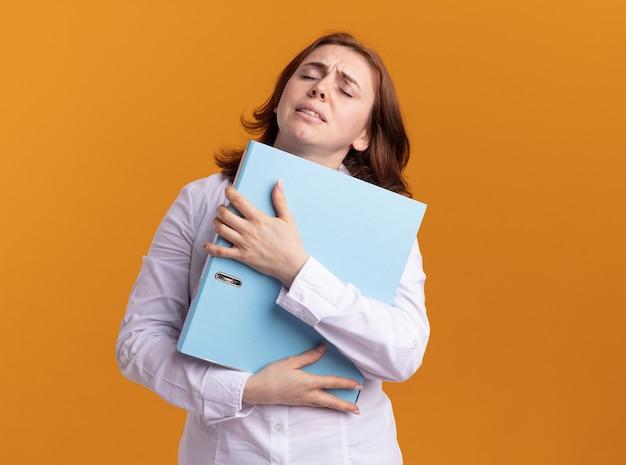 Молодая женщина в белой рубашке, держащая папку, выглядит уставшей и перегруженной, стоя у оранжевой стены