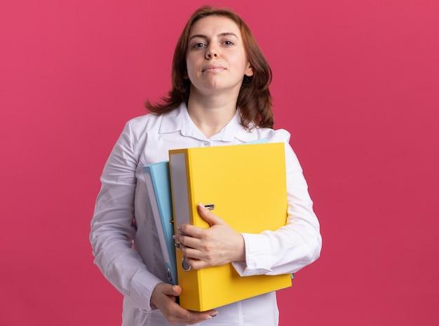 ピンクの壁の上に立っている真剣な自信を持って正面を見てフォルダーを保持している白いシャツの若い女性