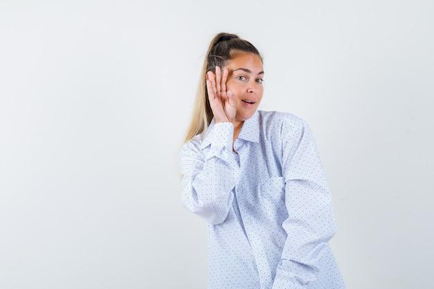 誰かを呼び出して幸せそうに見えるように顔の近くで手を握って白いシャツの若い女性