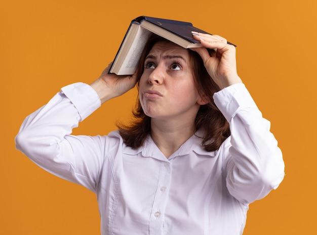 オレンジ色の壁の上に立って混乱して見上げる彼女の頭の上に開いた本を保持している白いシャツの若い女性
