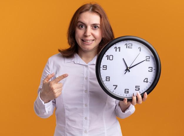 오렌지 벽 위에 서있는 얼굴에 미소로 정면을보고 벽 시계를 들고 흰 셔츠에 젊은 여자