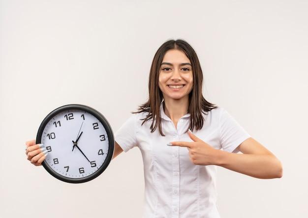 白い壁の上に元気に立って微笑んでそれを指で指している壁時計を保持している白いシャツの若い女性