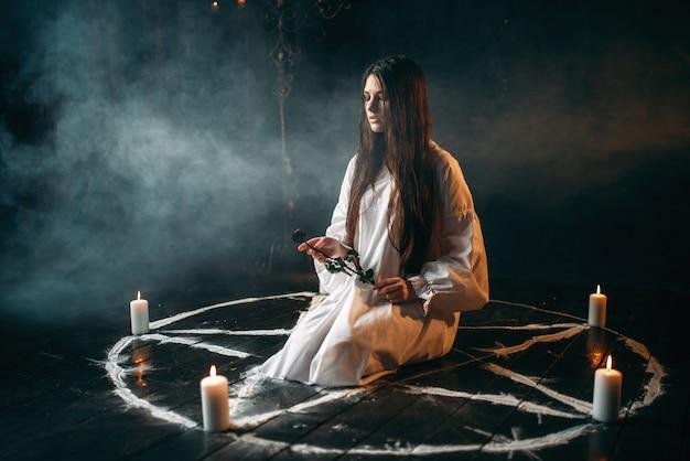 Молодая женщина в белой рубашке держит в руках сгоревшую розу, круг пентаграммы со свечами, кругом дым. ритуал темной магии, оккультизм