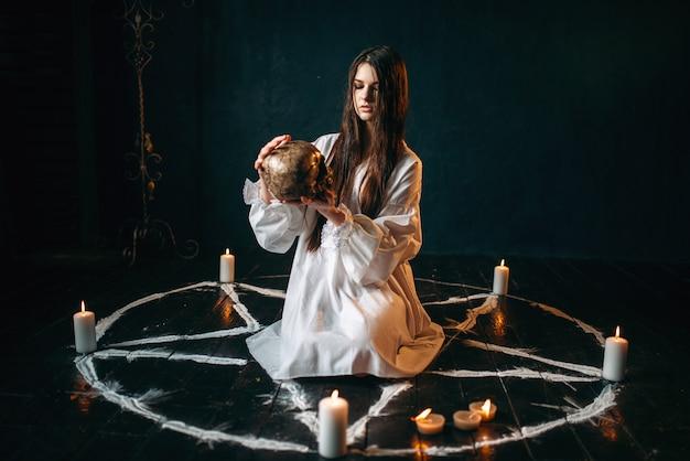 Молодая женщина в белой рубашке держит в руке человеческий череп, круг пентаграммы со свечами, кругом дым, ведьма. ритуал темной магии, оккультизм