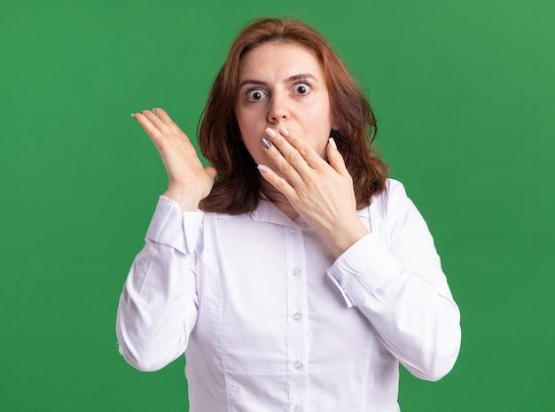 緑の壁の上に立っている手で口を覆ってショックを受けている正面を見て白いシャツの若い女性