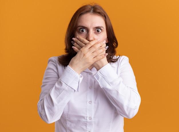 オレンジ色の壁の上に立っている手で口を覆ってショックを受けている正面を見て白いシャツの若い女性