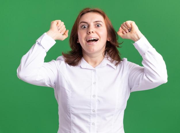 緑の壁の上に立って幸せで興奮して拳を上げる正面を見て白いシャツを着た若い女性