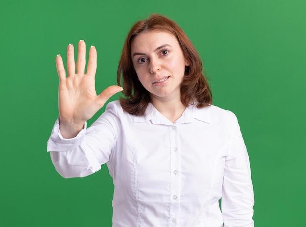 Молодая женщина в белой рубашке смотрит вперед, показывая пальцами номер пять, улыбаясь и глядя на зеленую стену
