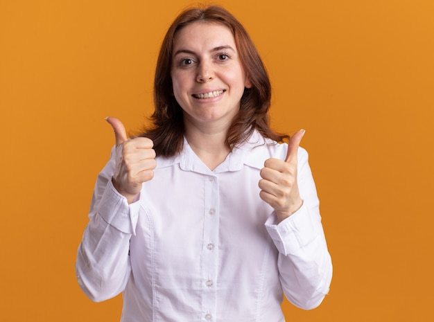 오렌지 벽 위에 서있는 엄지 손가락을 유쾌하게 보여주는 웃는 전면을보고 흰 셔츠에 젊은 여자