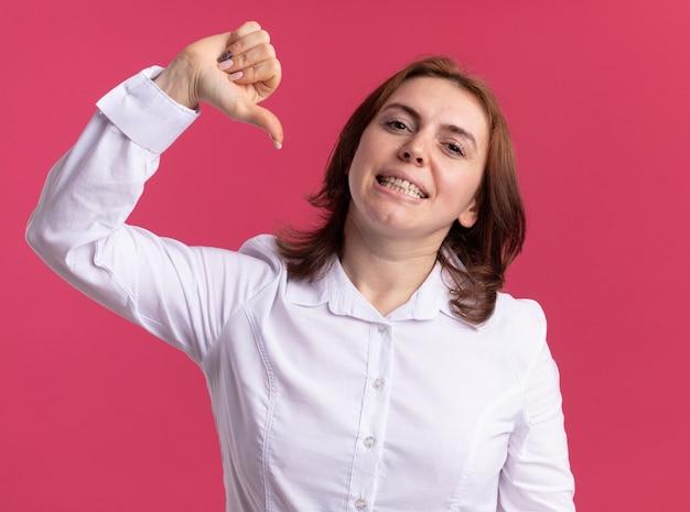 분홍색 벽 위에 서있는 엄지 손가락으로 자신을 가리키는 자신감 미소 앞에서 흰 셔츠를 입은 젊은 여자
