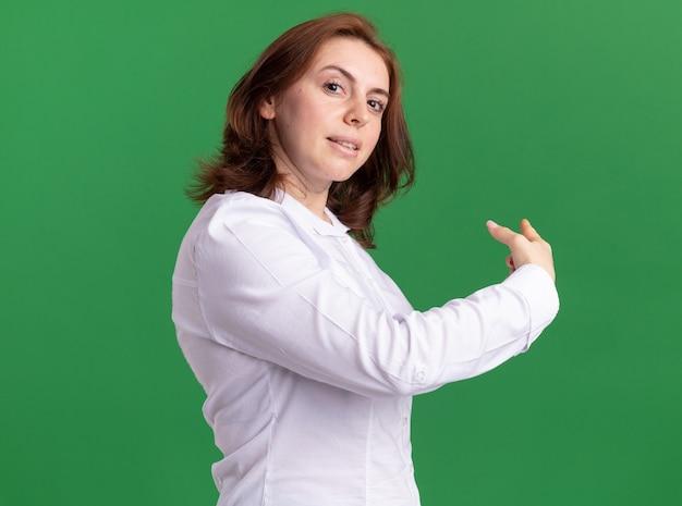 흰색 셔츠에 젊은 여자가 녹색 벽 위에 다시 서있는 자신감을 가리키는 미소 앞에보고