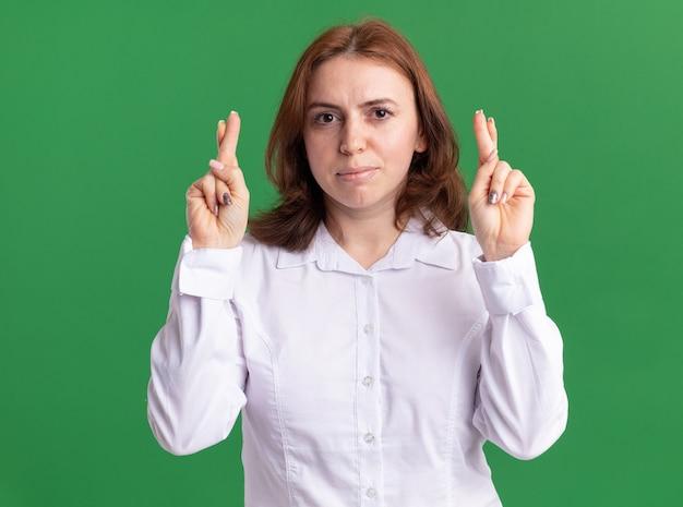 녹색 벽 위에 서 심각한 얼굴 횡단 손가락으로 정면을보고 흰 셔츠에 젊은 여자
