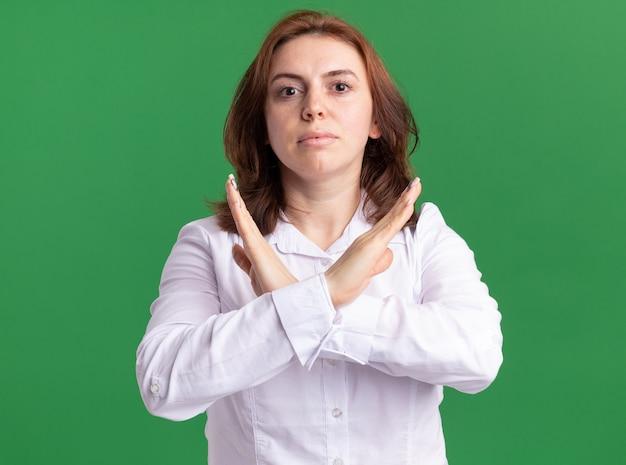 녹색 벽 위에 서 심각한 얼굴 교차 손으로 정면을보고 흰 셔츠에 젊은 여자