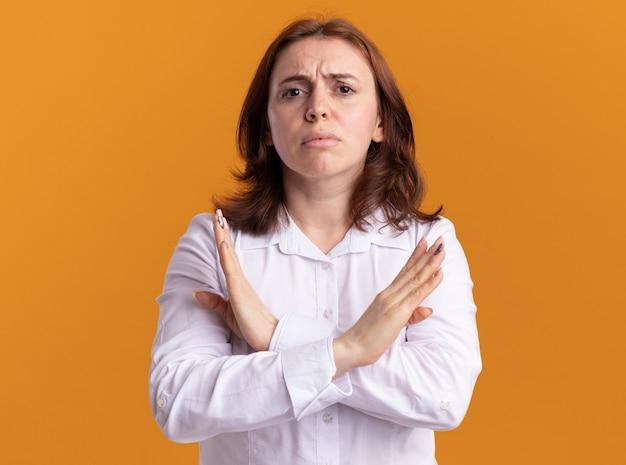 오렌지 벽 위에 서있는 손을 건너는 중지 제스처를 만드는 심각한 얼굴로 정면을보고 흰 셔츠에 젊은 여자