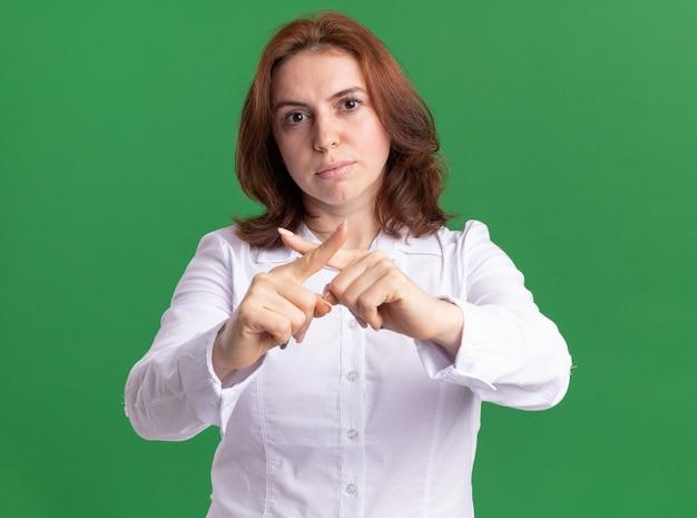 Молодая женщина в белой рубашке смотрит вперед с серьезным лицом, делая жест стоп, скрещивая указательные пальцы, стоя над зеленой стеной
