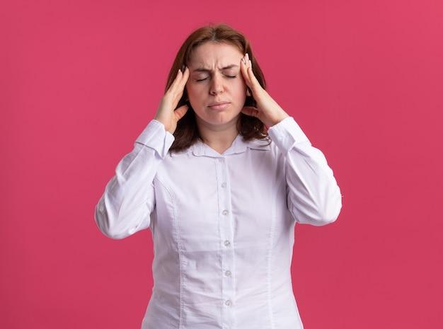 ピンクの壁の上に立っている頭痛に苦しんでいる彼女の寺院に触れて体調不良に見える白いシャツの若い女性