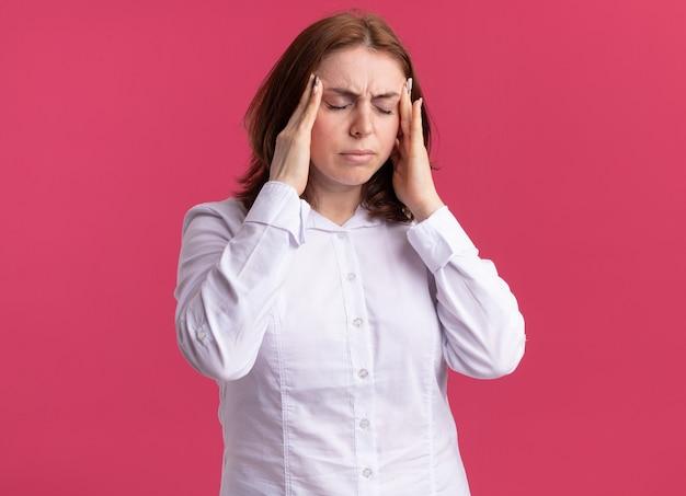 Молодая женщина в белой рубашке выглядит нездоровой, касаясь своих висков, страдая от головной боли, стоя у розовой стены
