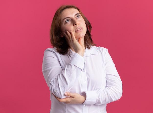 ピンクの壁の上に立って考えて彼女の頬に手で見上げる白いシャツの若い女性