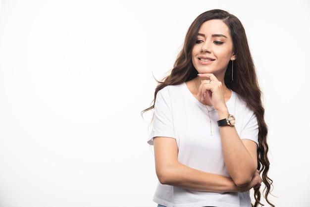 白い背景にポーズをとって白いシャツを着た若い女性。高品質の写真