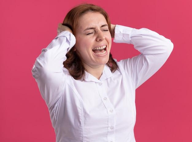 분홍색 벽 위에 서있는 그녀의 머리에 손으로 짜증이 표정으로 외치는 흰 셔츠에 젊은 여자